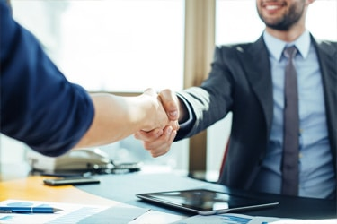 A smiling young man shakes hands with someone off camera to seal a business deal