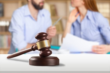 An arguing couple going through a divorce are sitting in a lawyer's office with paperwork