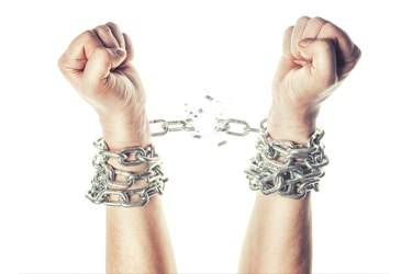 Two hands breaking free from chains around the wrists