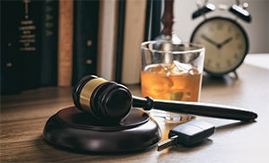 A desk with a gavel, car keys, and a glass filled with alcohol, indicating a DUI case