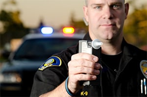 A police officer holds up a breathalyzer to test someone for driving under the influence