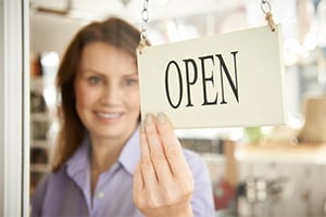 Business law concept, a woman business owner flips the sign on the shop door to show it is now open.