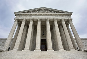 On the steps of the Supreme Court of the United States, looking up at the towering columns