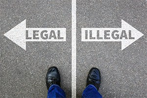 Looking down at a pair of feet straddling a white line on the pavement. One side has an arrow that says Legal and the other an arrow that says Illegal.