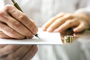 Man signing divorce papers with his wedding ring on the table next to him