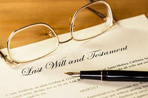A copy of a last will and testament is laying on a table with a pen ready to sign it and a pair of glasses next to it