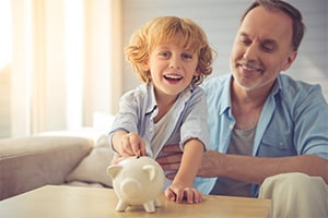 An older man is holding his grandson while the young boy puts money into a piggy bank on the table