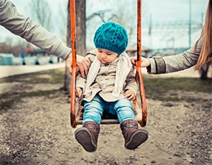 A toddler is on a swing with an arm from each parent on either side of the swing