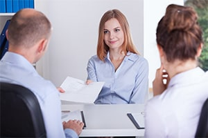 Woman at a job interview after clearing her criminal record hands her resume to the interviewers
