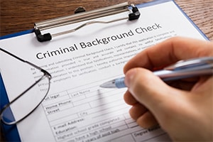 Close up of a hand holding a pen to fill out a form for a criminal background check