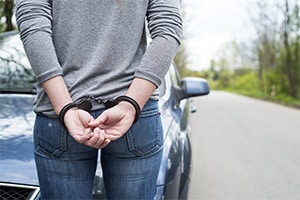 Recently arrested woman in handcuffs standing in front of her car on the side of the road