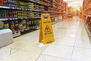 Concept photo for personal injury caused by negligence of a wet floor sign in a grocery store aisle