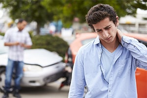 A young man rubs his neck in pain while standing in front of two cars that have crashed into each other