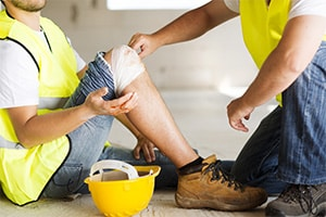 A man wearing construction gear bends down to help another man in construction gear who has injured his knee