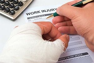 A close up of a man's hands filling out a work injury report. One hand is heavily bandaged.