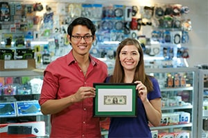 Small business law concept - Two small business owners stand in front of the counter at their shop holding their framed first dollar